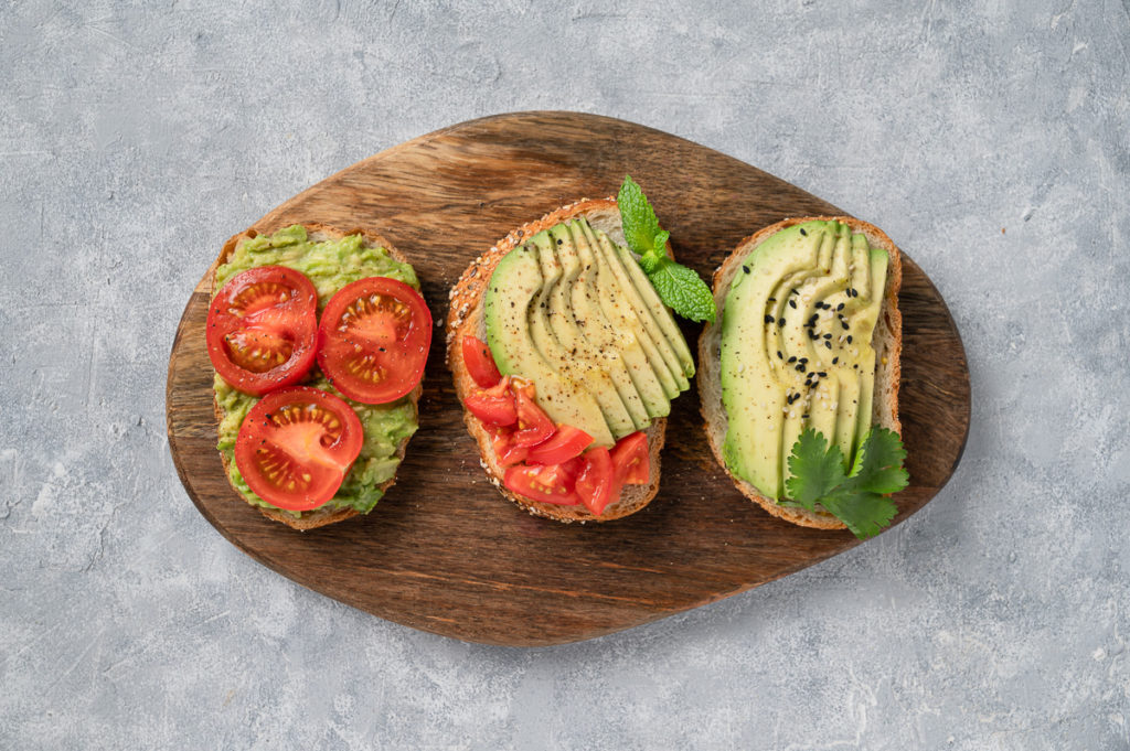 Avocado toasts food photography with tomatoes, smashed and cut avocados, tomatoes, cilantro, mint leaf, sesame seeds, salt and pepper on a wooden cutting board