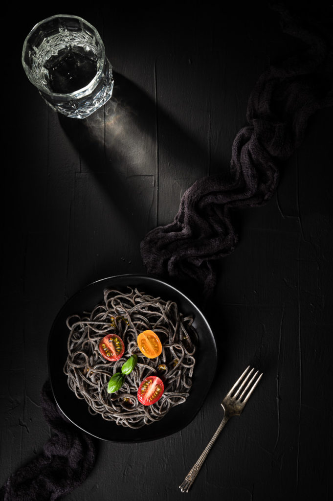 Restaurant food photography with black pasta with basil, cherry tomatoes, fork, black napkin on black background