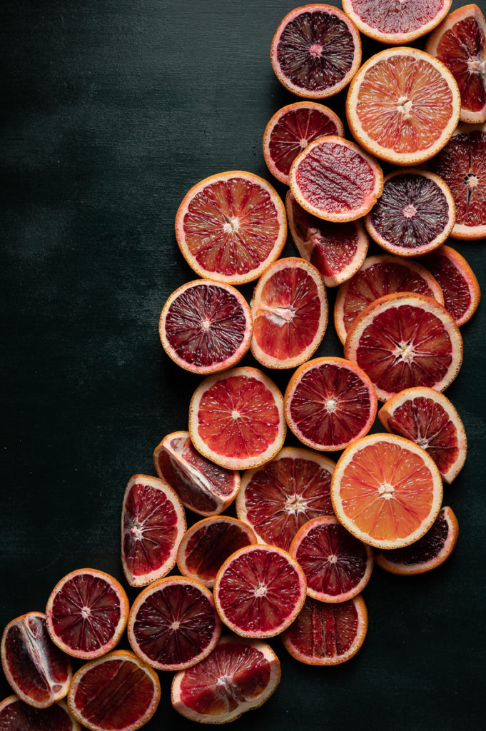 Blood oranges fruit photography, cut oranges on green background