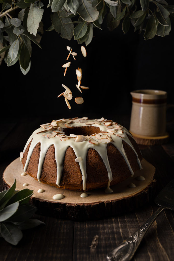 Dark food photography of almond cake with white chocolate on top, green leaves and flying almond flakes