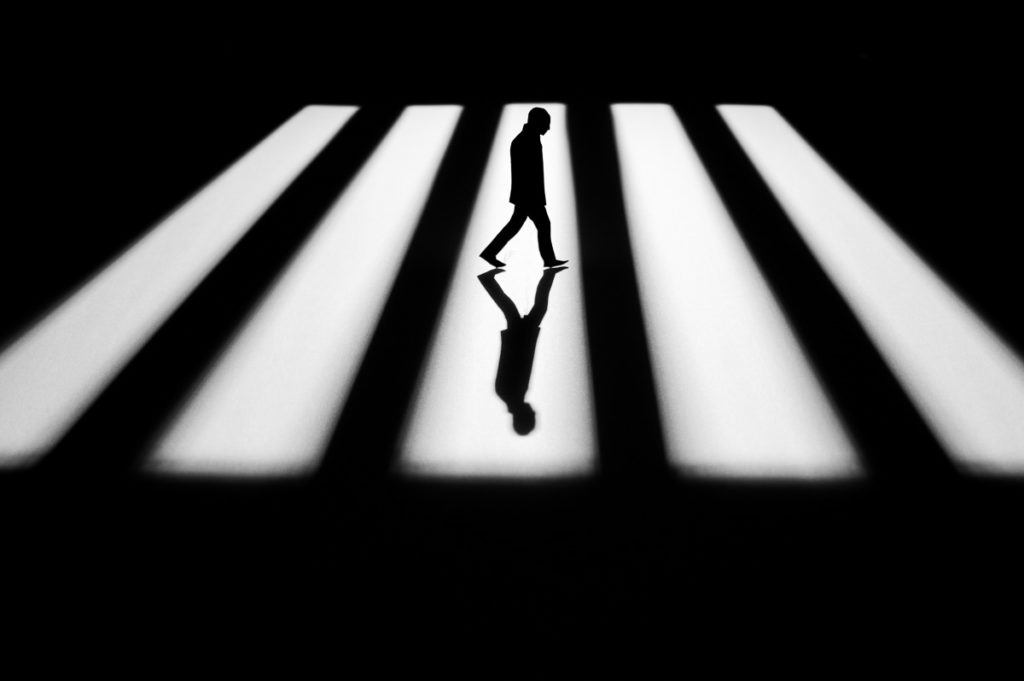 Black and white photography of a man walking