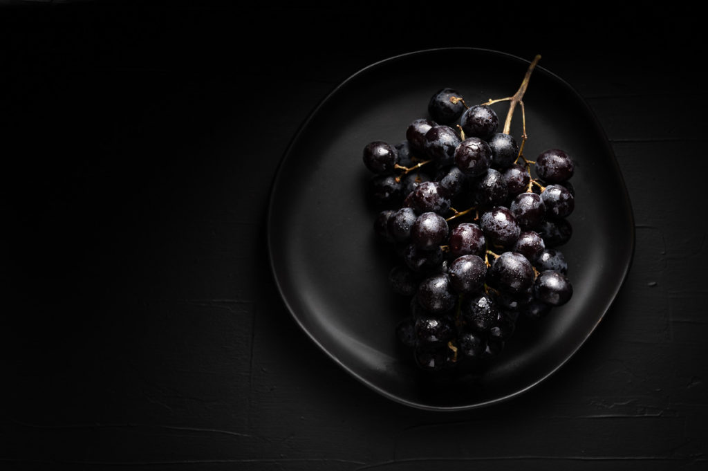 Dark and moody food photography of black grapes on black background
