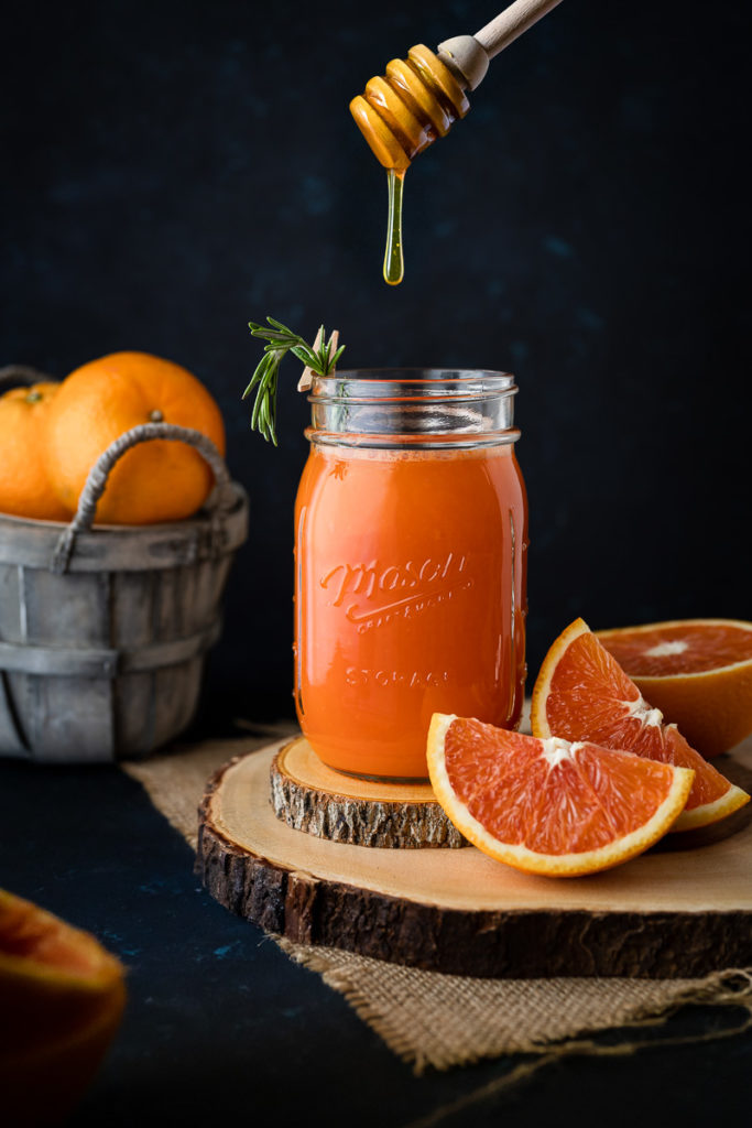Healthy orange and carrot juice with rosemary leaves, honey