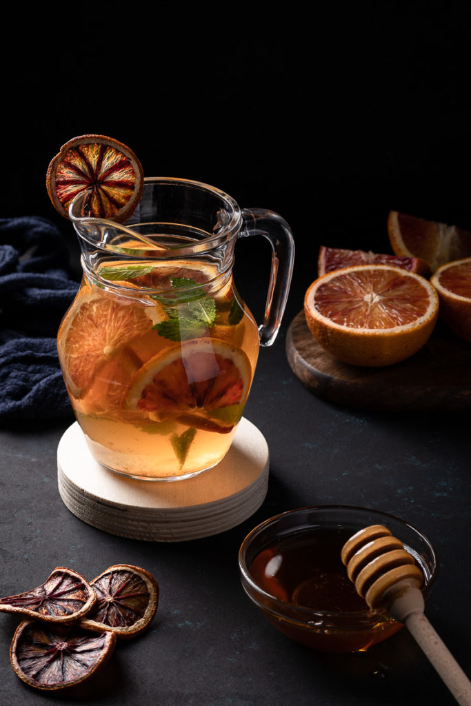 Drink photography blood orange and mint tea with honey on dark background