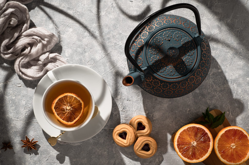 Photography cup of orange tea with cookies, star anise, teapot at sunrise