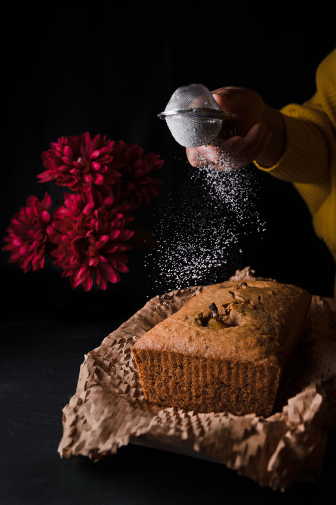 Dark food photography of a pear cake with powdered sugar using a strainer