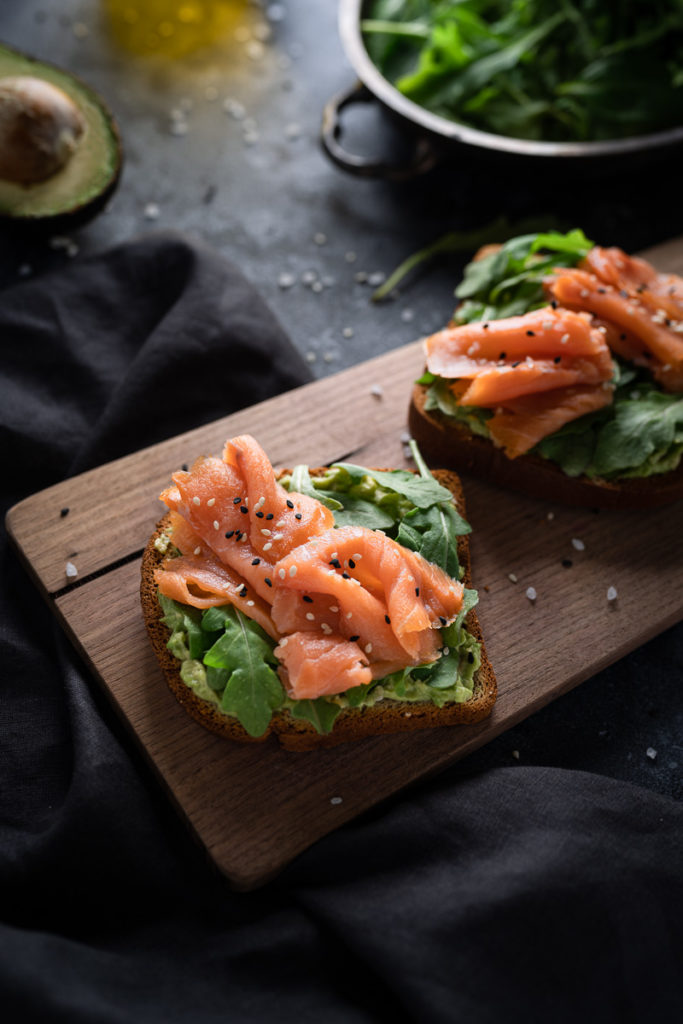 Food photography of avocado and salmon toast with arugula, salt, pepper and sesame seeds