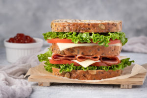 Food photography of sandwich with ham, lettuce, tomato, cheese, bread, ketchup