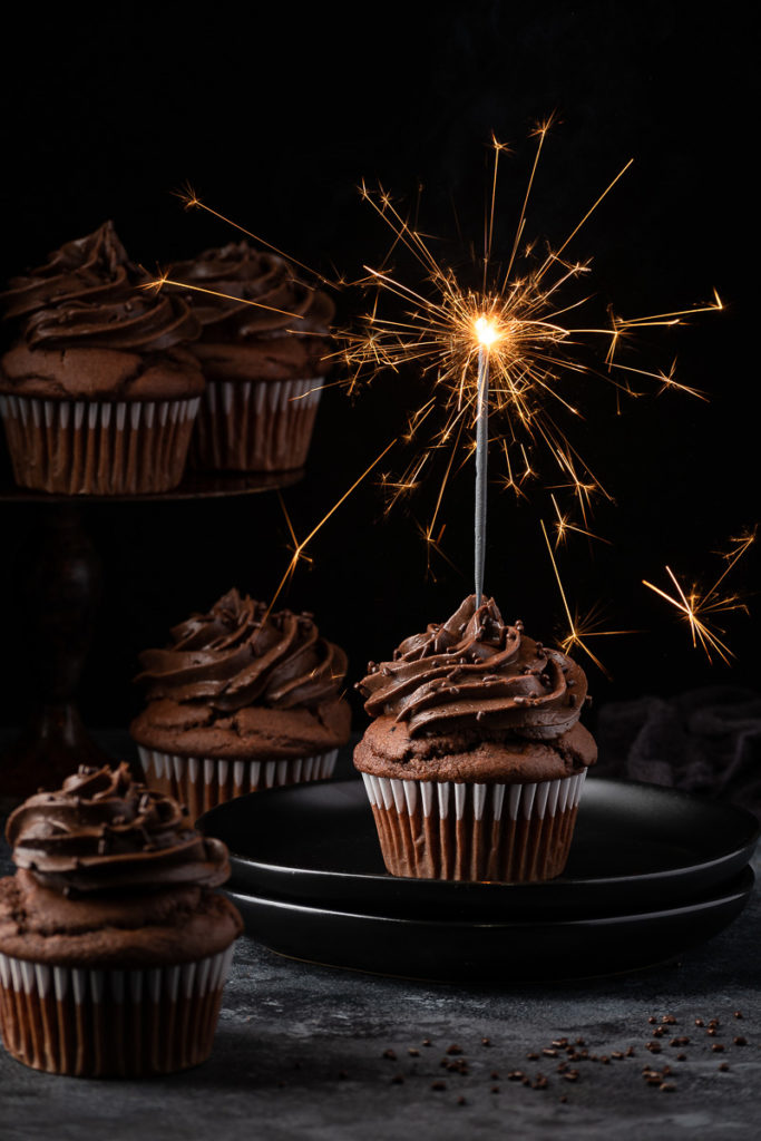 Chocolate cupcake food photography with sparkles, chocolate chips and chocolate frosting