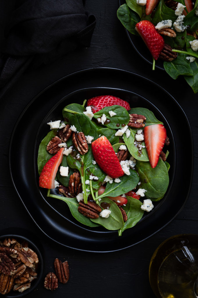 Restaurant photography spinach salad with strawberries, walnuts, feta cheese and dressing