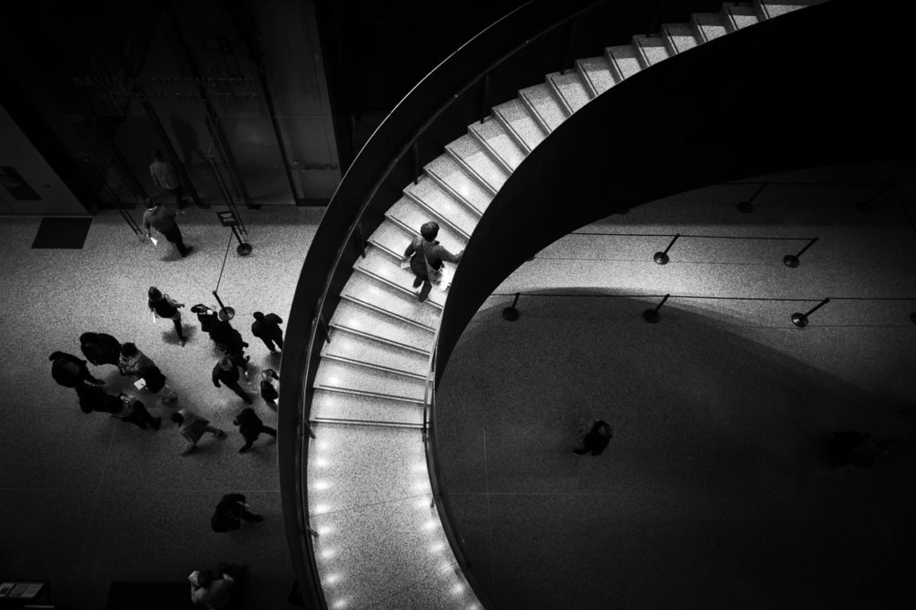 Black and white photography of a woman climbing stairs