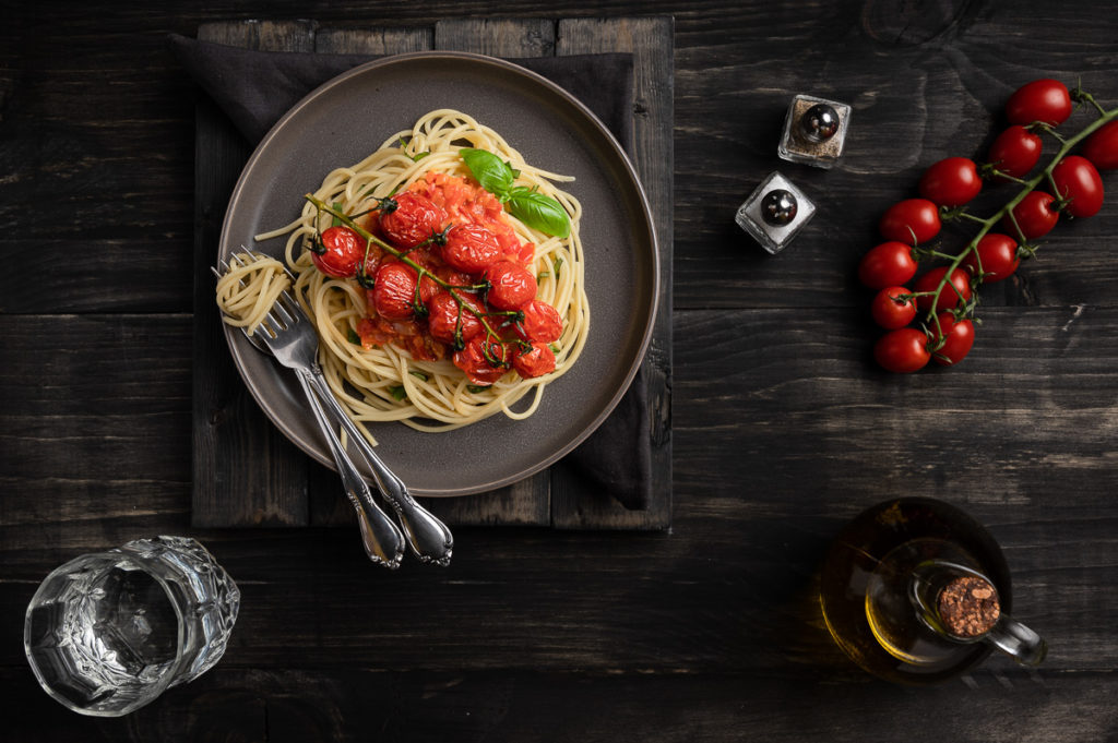 Restaurant photography with tomato pasta with basil, tomato sauce, salt, pepper, olive oil, tomatoes on the vine