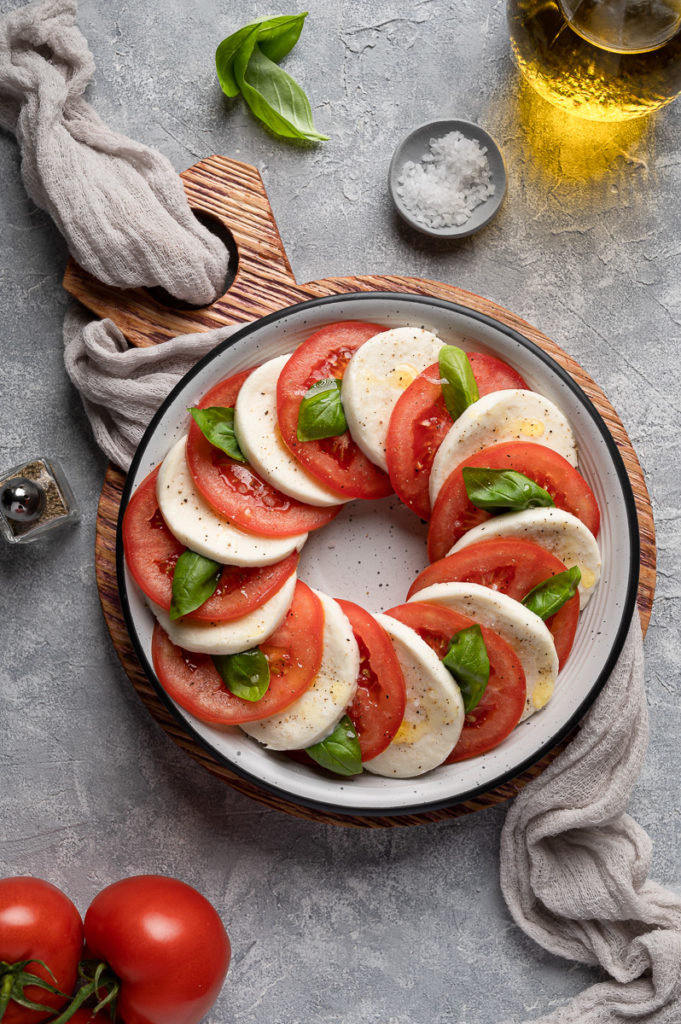 Food photography caprese salad tomatoes, fresh basil leaves, mozzarella cheese, salt, pepper and olive oil