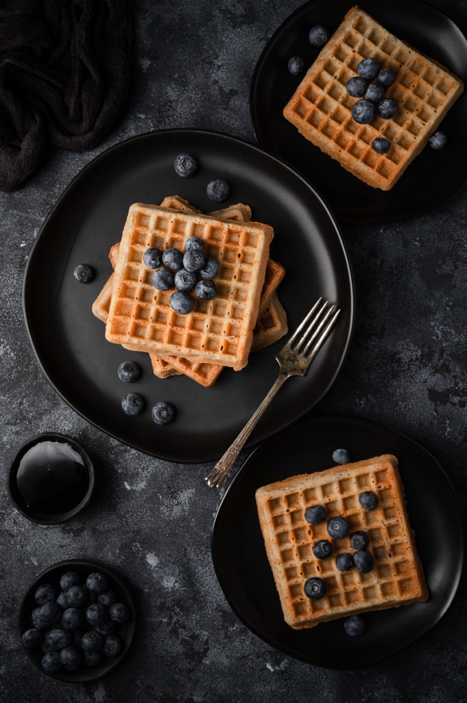 Blueberries waffles maple syrup food photography on black plates and black background