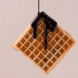 Food photography levitating waffle with melted chocolate