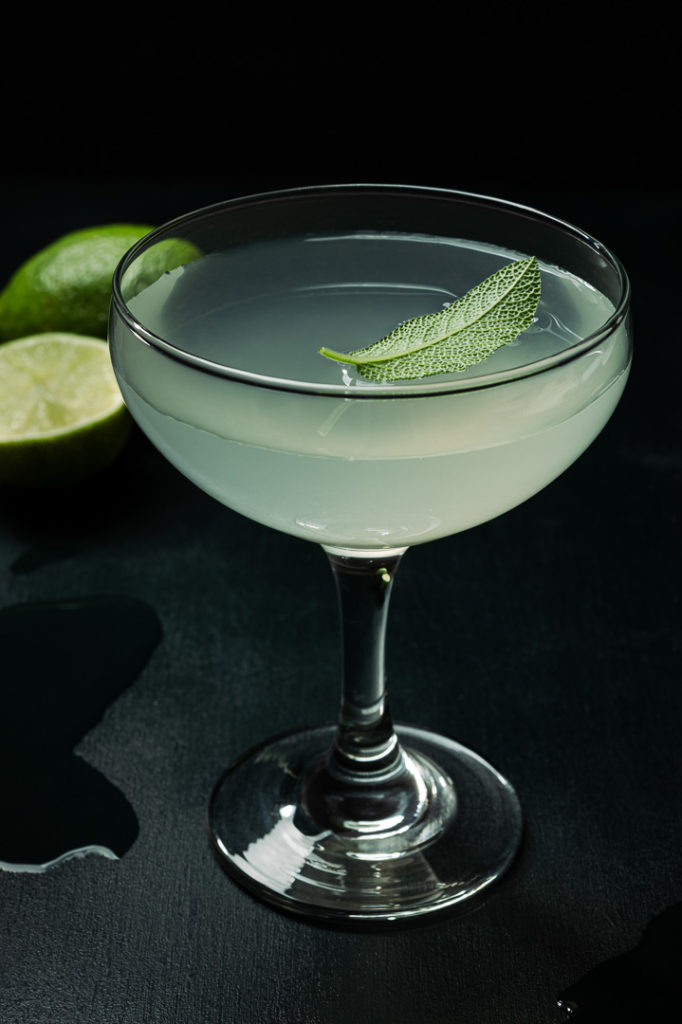 Dark and moody photography of lime cocktail styled with sage leaf and cut limes on a deep green background
