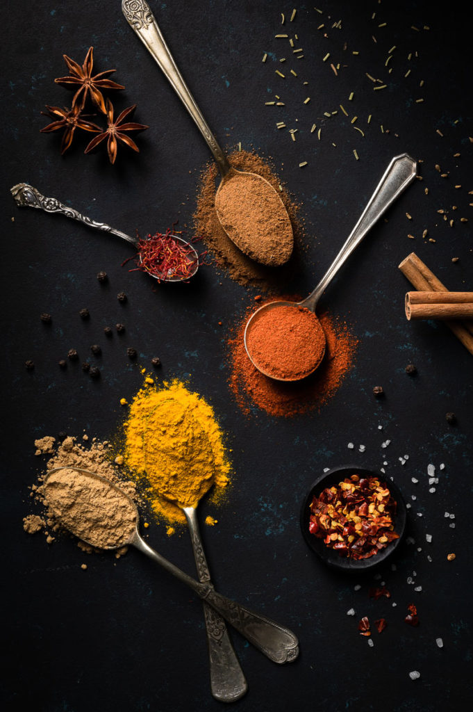 Mixed spices paprika turmeric cinnamon pepper flakes star anis saffron on dark background