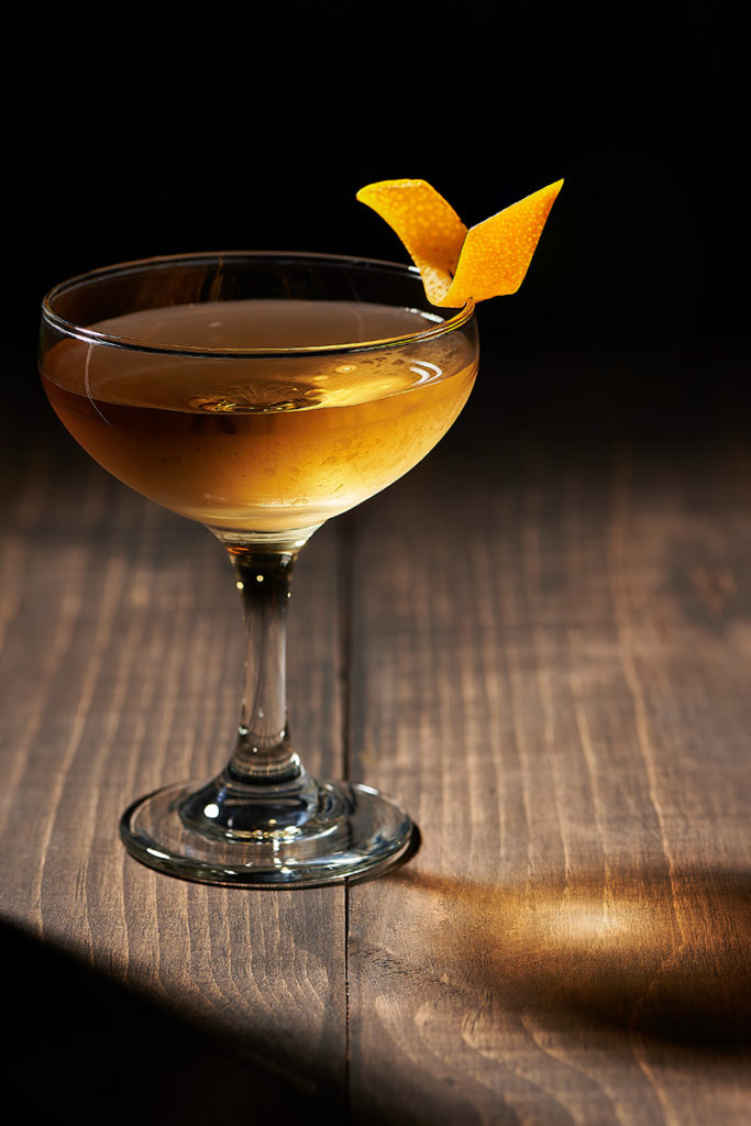 Photography of cocktail with orange garnish on wooden surface